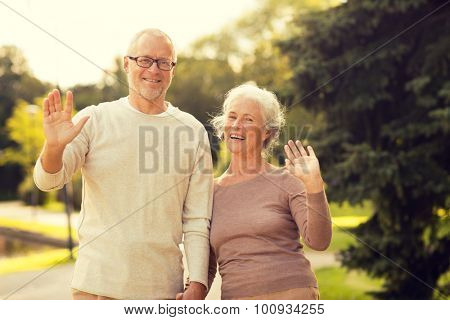 family, age, tourism, gesture and people concept - senior couple waving hands in city park