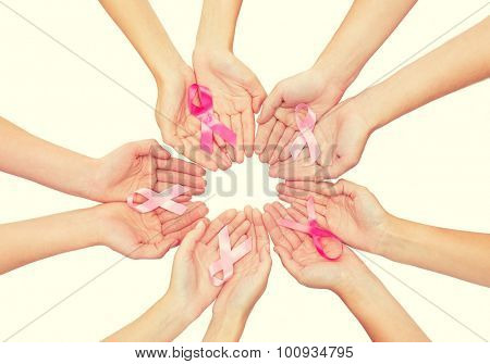 healthcare, people and medicine concept - close up of women hands with cancer awareness ribbons over white background