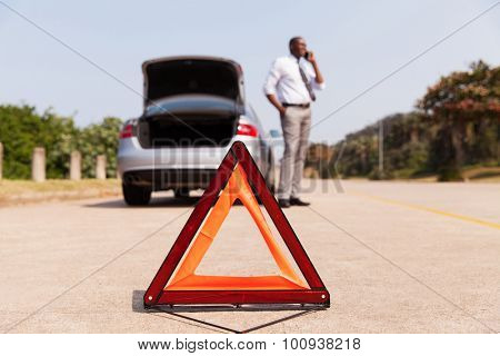 african male driver calling for help after car broke-down by the side of the road