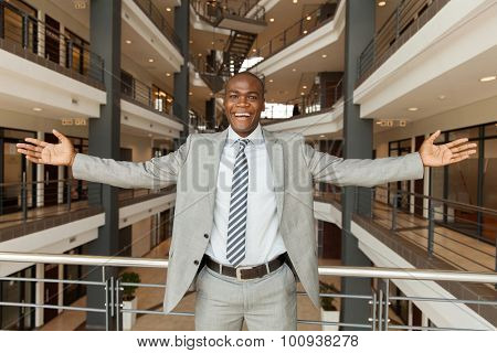 excited african businessman with arms outstretched in modern office building