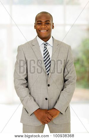 handsome young african american businessman standing in office