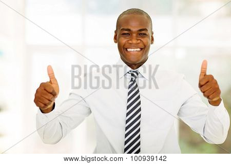 good looking african business man with thumbs up in modern office