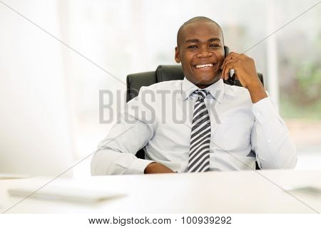 african business man talking on landline phone in modern office