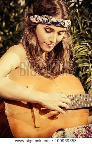 Joyful hippie girl playing the guitar outdoor in the sunny summer day. Child of nature. Lifestyle. Toned photo, sepia.