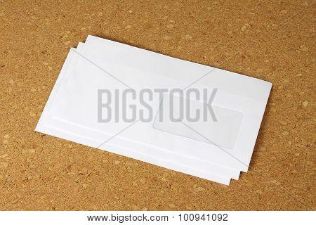 White Envelope On Corkboard Background.