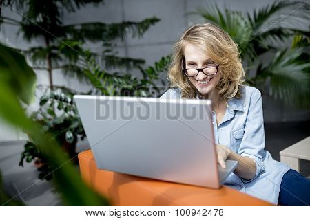 Young businesswoman using laptop in office with happy expression