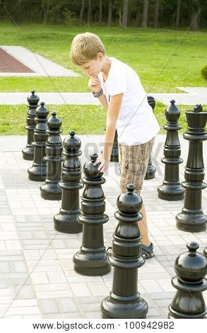 Boy with chessmen is in the street on the stone chessboard