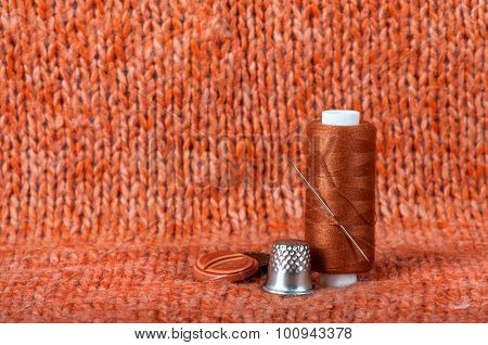 Needle With Thread And Buttons On A Fabric Background
