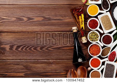 Various spices and condiments on wooden background with copy space