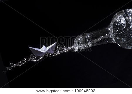 Paper Boat Rides On A Water Splash Out Of A Bottle Against Black Background