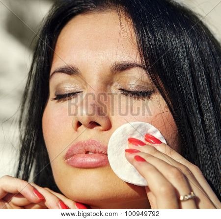 close up of girl who cleans her face by tonic