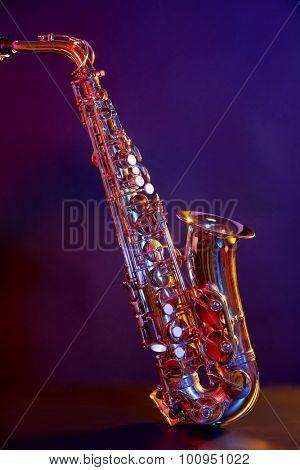 Golden saxophone on purple background