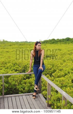 Woman and walkway made from wood and mangrove field