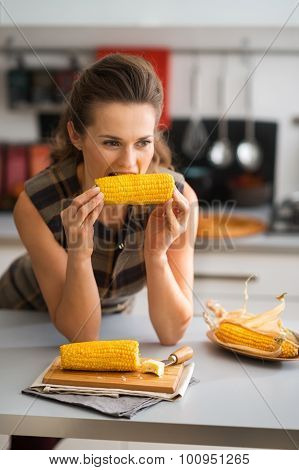 Woman Biting Into Corncob While Leaning On Kitchen Counter