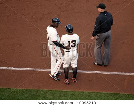 Coach Roberto Kelly Talks To Player Cody Ross On 1St Base Line After He Was Hit By A Pitch