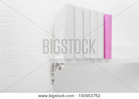 Blank books and pink one on shelf on white wallpaper background