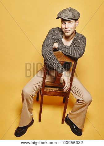 Expressive Man Sits On The Chair And 70's Look Theme
