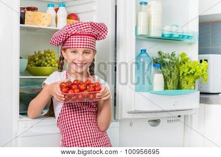 little girl cook holding tomatoes near opened fridge