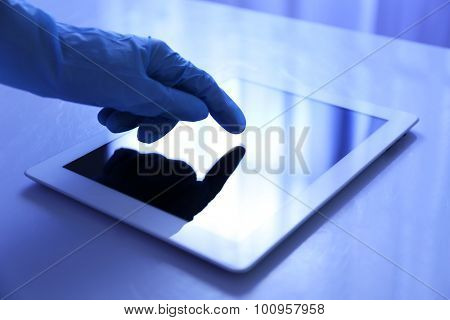 Doctor hand in rubber glove using tablet in office