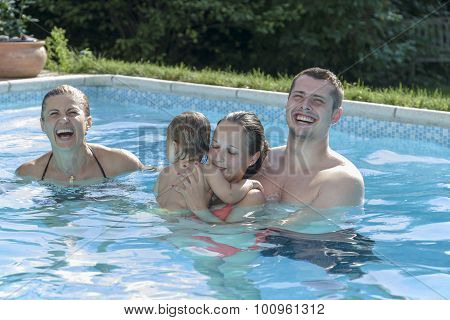 Family Enjoying A Pool