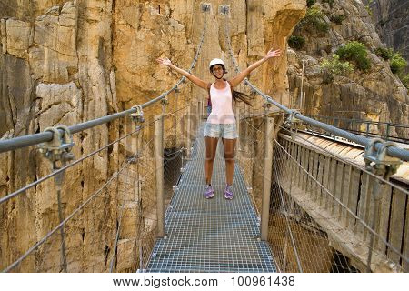 Woman In The Middle Of A Suspension Bridge In The Caminito Del Rey, Malaga, Spain.