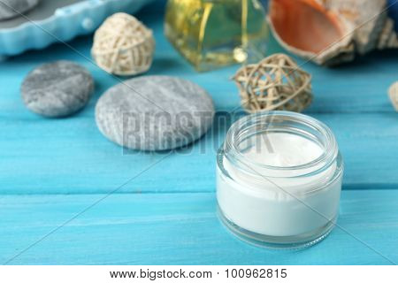 Stack of spa stones and spa treatments on color wooden background