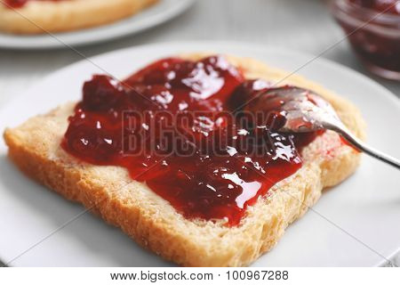 Bread with butter and homemade jam in white plate, closeup