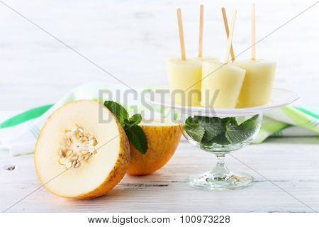 Melon ice lolly on table on light blurred background