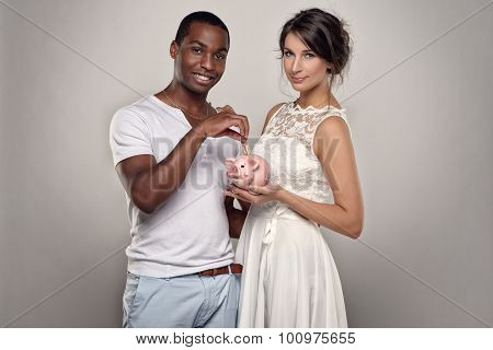 Young Couple With Piggy Bank Smiling At The Camera