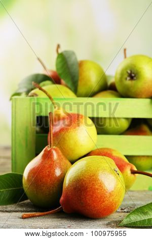 Fresh pears in crate on wooden table on blurred background