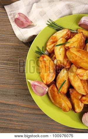 Baked potato wedges on wooden table, top view