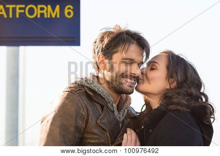 Closeup of young brunette woman kissing her man at railway station. They are waiting outdoor at platform. The man is smiling with joy while his girl is kissing him on the cheek.