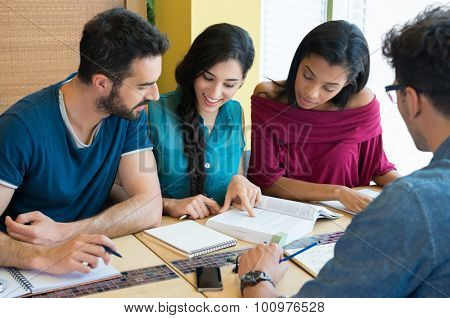 Closeup shot of young man and woman discussing on note. Happy and smiling student studying at the library. Multi ethnic group studying on book for the next exam.