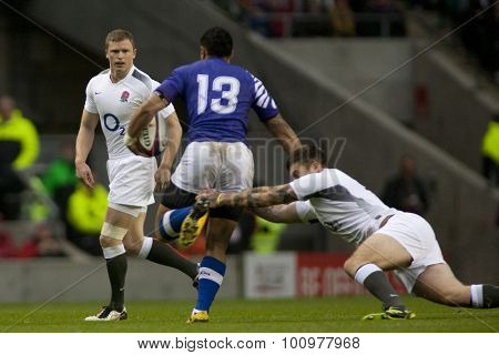 TWICKENHAM LONDON, 20 NOVEMBER 2010. England's Chris Ashton, watches on as England's Matt Banahan, tackles Samoa's George Pisi,  during the International match between England and Samoa