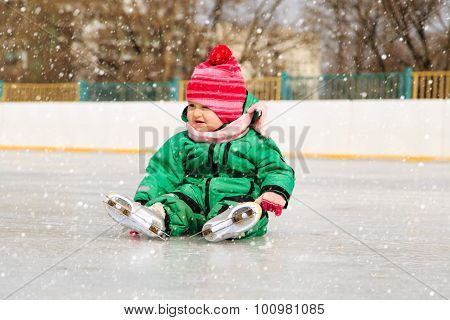 little girl sitting on ice with skates after the fall