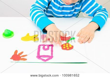 little boy playing with clay dough, education and daycare