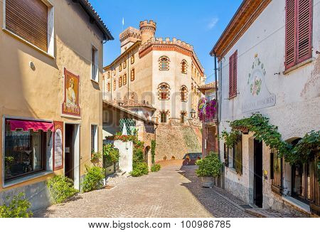 BAROLO, ITALY - AUGUST 26, 2015: Narrow street, old houses and medieval castle of Barolo - first built in X century by feudal family Falletti, restored and changed many times during the years.
