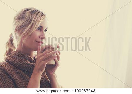 Woman wearing warm knitted sweater is drinking cup of hot tea or coffee near window in autumn mornin