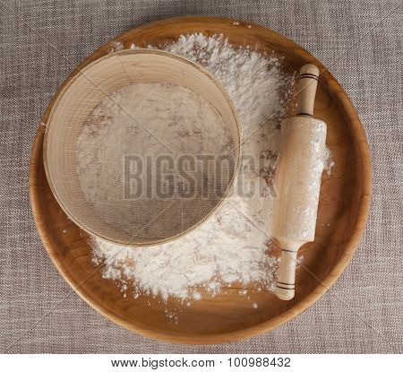 Rolling pin and sieve in the flour on a wooden tray. Composition on a beautiful tablecloths canvas. Photos for magazines about cooking, confectionery, cooking.