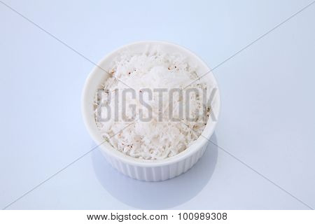 Top view of a small white bowl filled with shredded coconut on a white background.