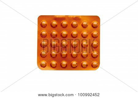 Orange pills in a blister pack isolated on white background