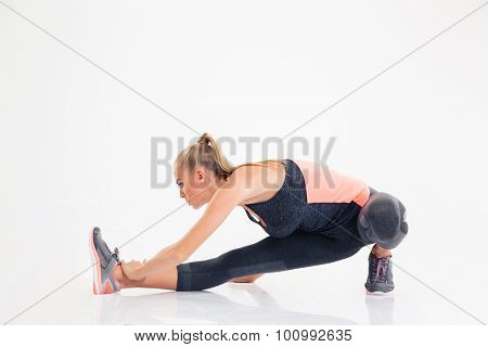 Full length portrait of a woman doing stretching exercises isolated on a white background