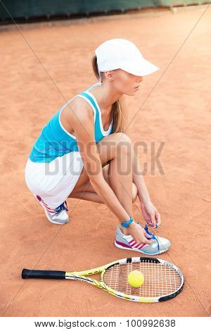 Female tennis player tying shoelaces outdoors