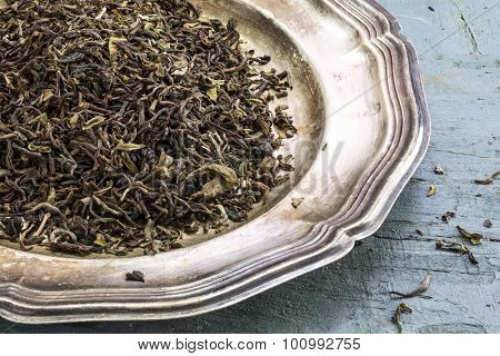 Loose Black Darjeeling Tea On A Silver Plate On Rustic Blue Painted Wood,