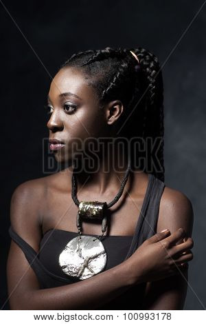 African Woman  With An Ethnic  Necklace Looks To The Left.