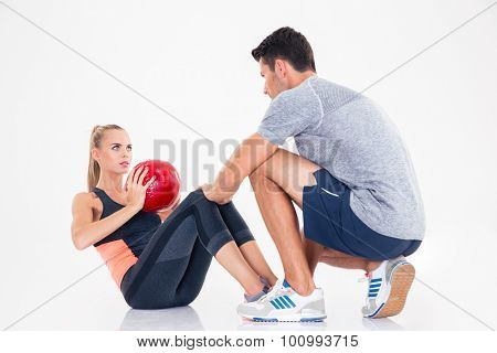 Portrait of a sports woman doing abs exercises with weight ball isolated on a white background