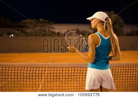 Back view portrait of a female tennis player with racket at court