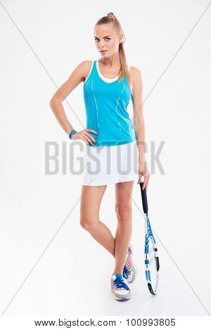 Full length portrait of a serious female tennis player standing isolated on a white background