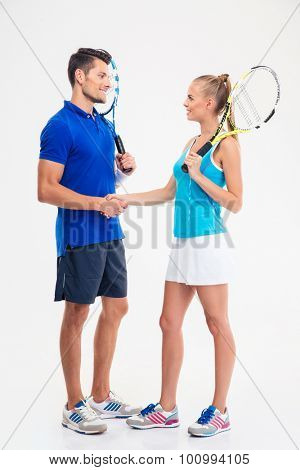 Full length portrait of a two tennis players making handshake isolated on a white background