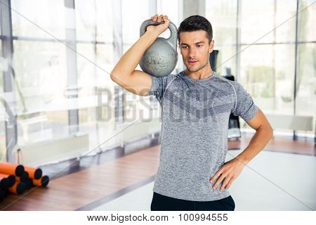 Portrait of a handsome fitness man workout with kettle ball in gym